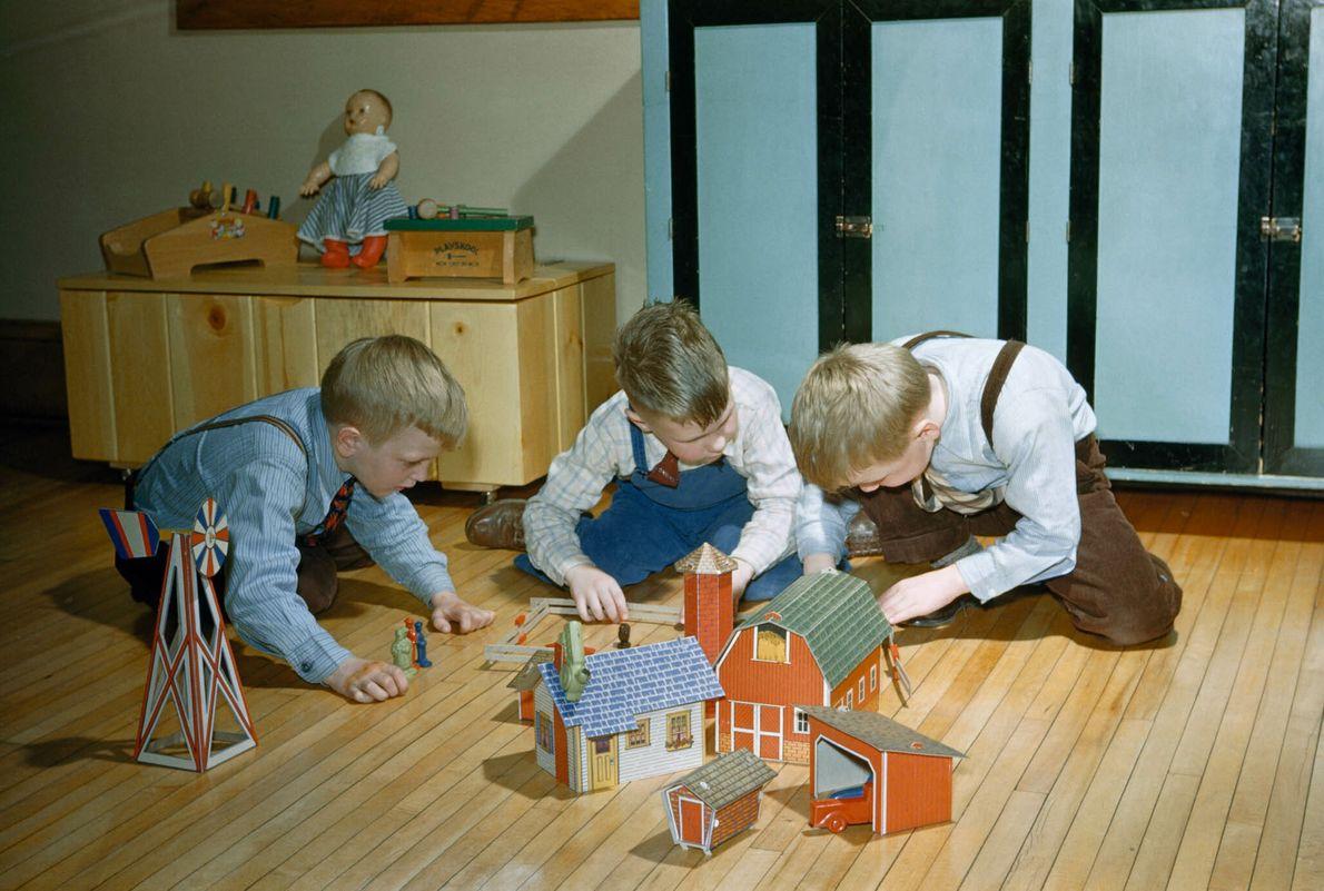 Drei Jungen sitzen mit einer Spielzeugfarm auf dem Boden