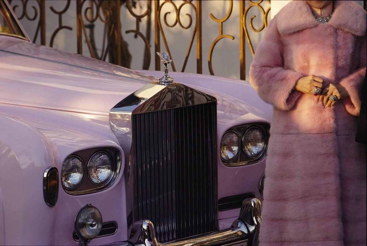 Eine Frau im rosa Nerzmantel posiert neben ihrem rosa Rolls Royce