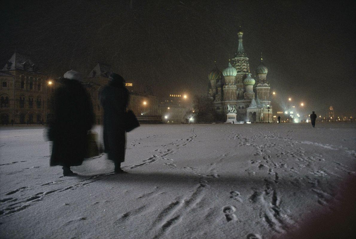 Frauen laufen durch den Schnee zur Basilius-Kathedrale in Moskau