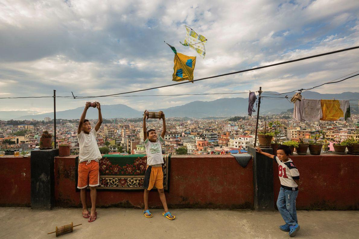 Kinder lassen auf einem Hausdach Drachen steigen