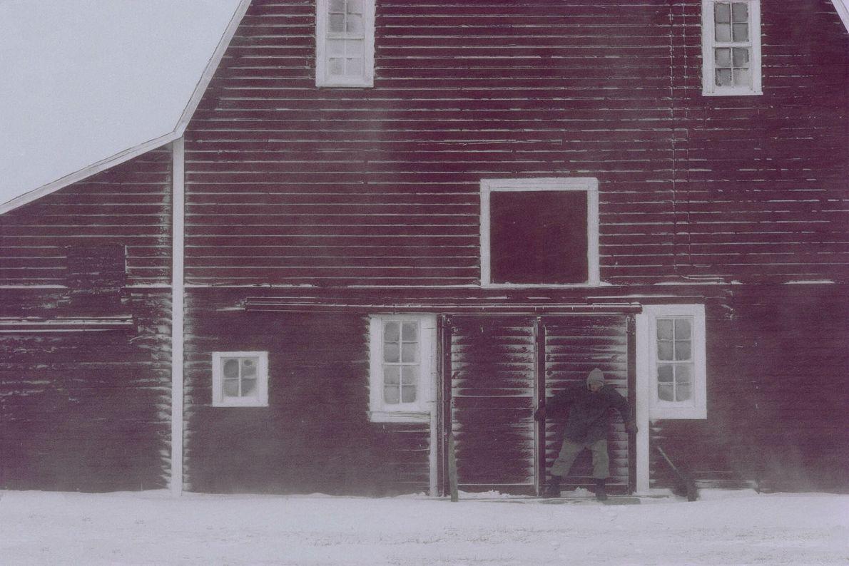 Mann steht im Schnee vor einer Scheune