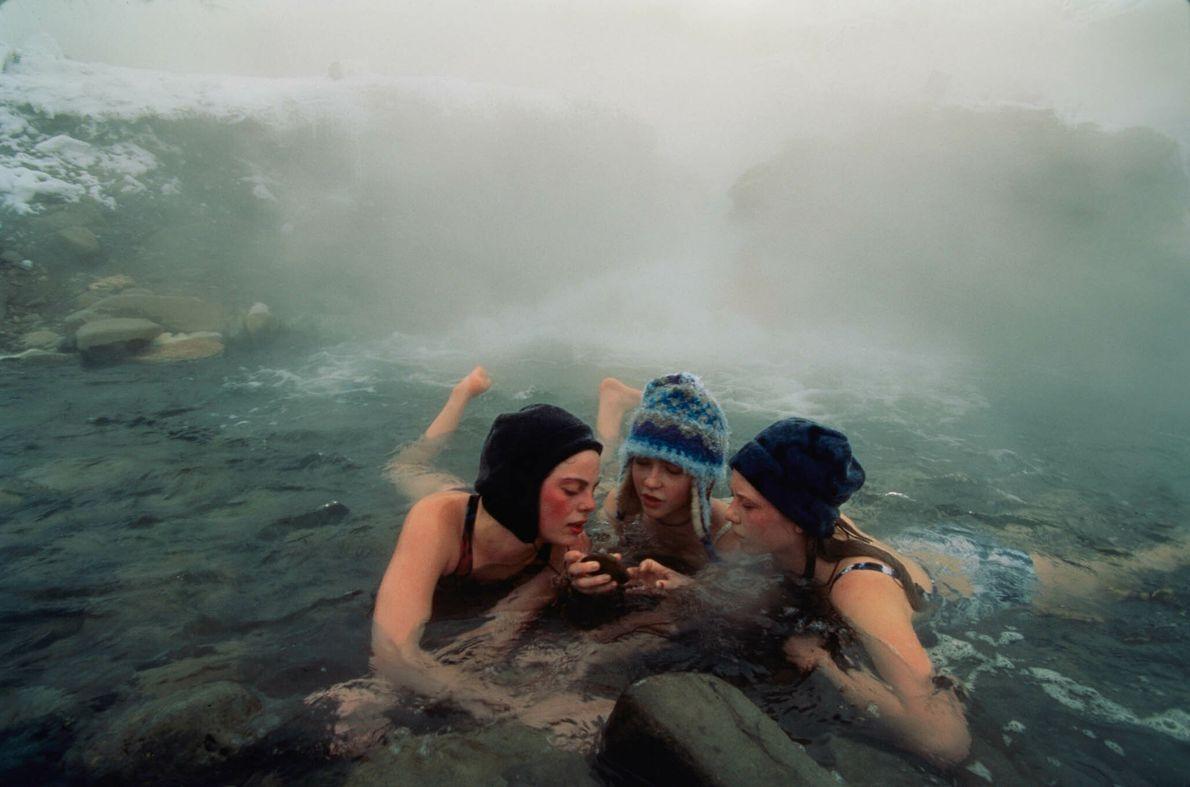 Junge Frauen mit Mützen baden in einer heißen Quelle