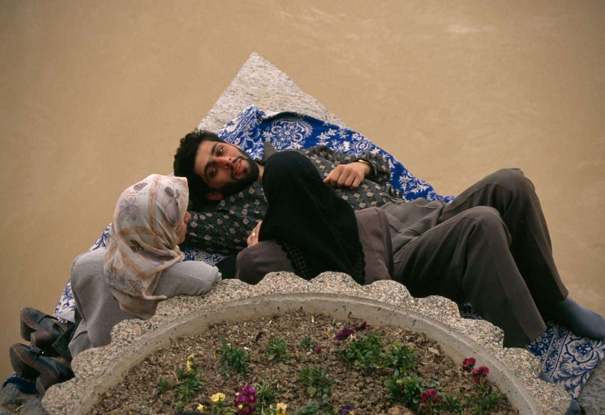 Drei Menschen sitzen und liegen auf einem Steinsockel