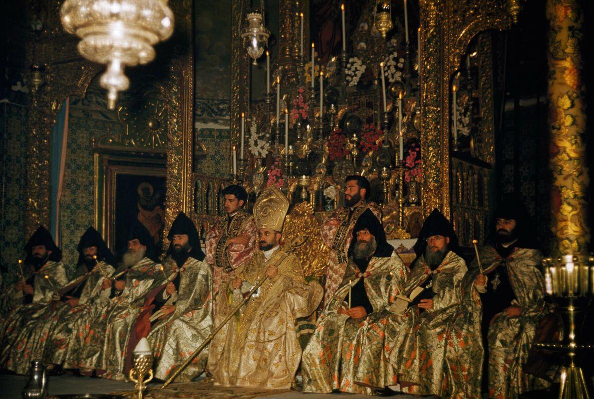 Festlich gekleidete Mönche sitzen in einem Gotteshaus