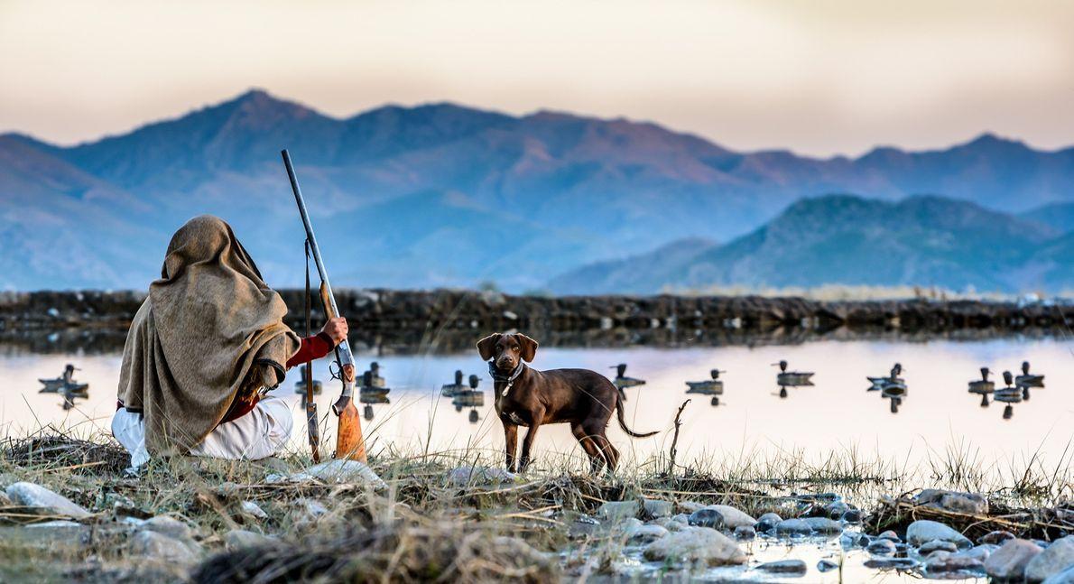 Ein Jäger und sein Hund warten an einem See mit Entenködern
