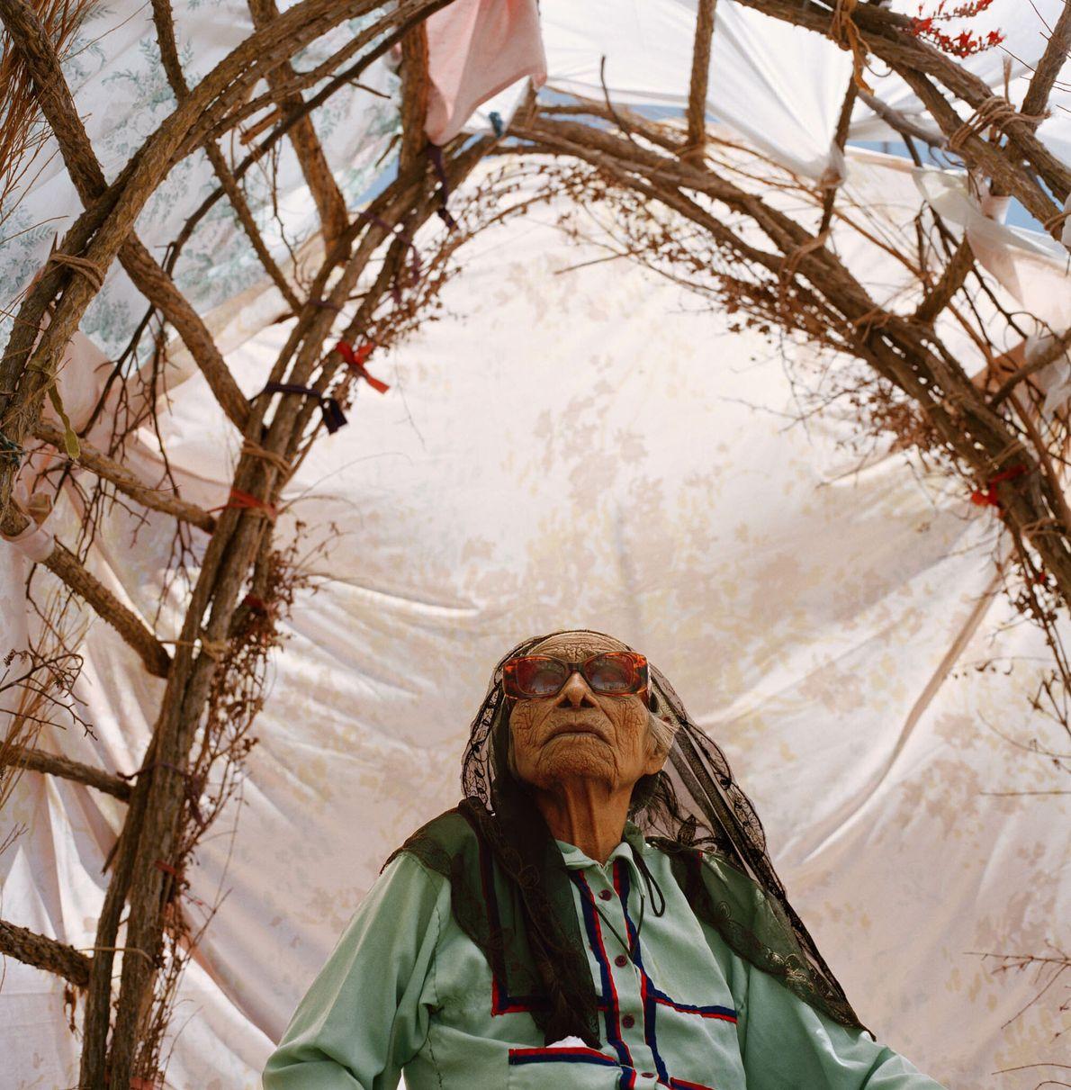 Alte Frau in einem Unterstand aus geflochtenen Weiden