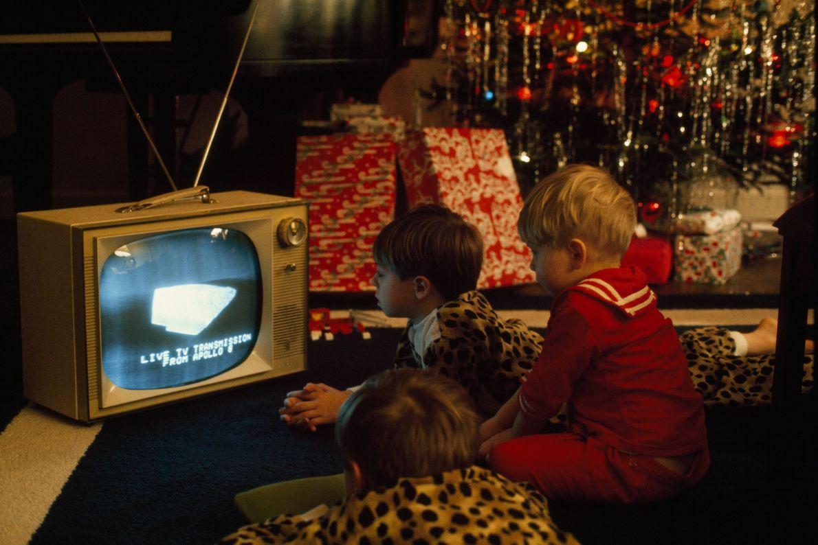 Kinder sehen zu Weihnachten im Fernsehen eine Apollo-Übertragung