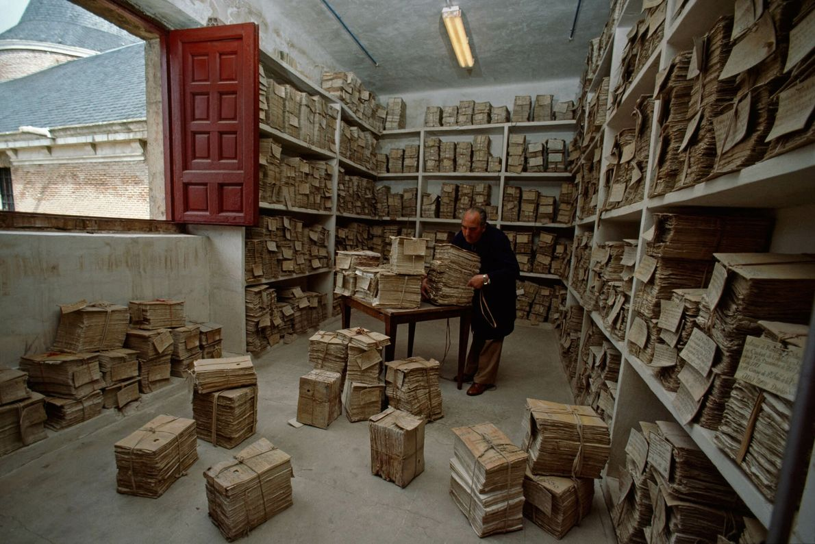 Mann in einem Raum mit Papierstapeln
