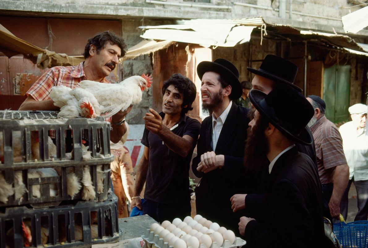 Chassidische Männer begutachten auf einem Markt in Jerusalem Hühner