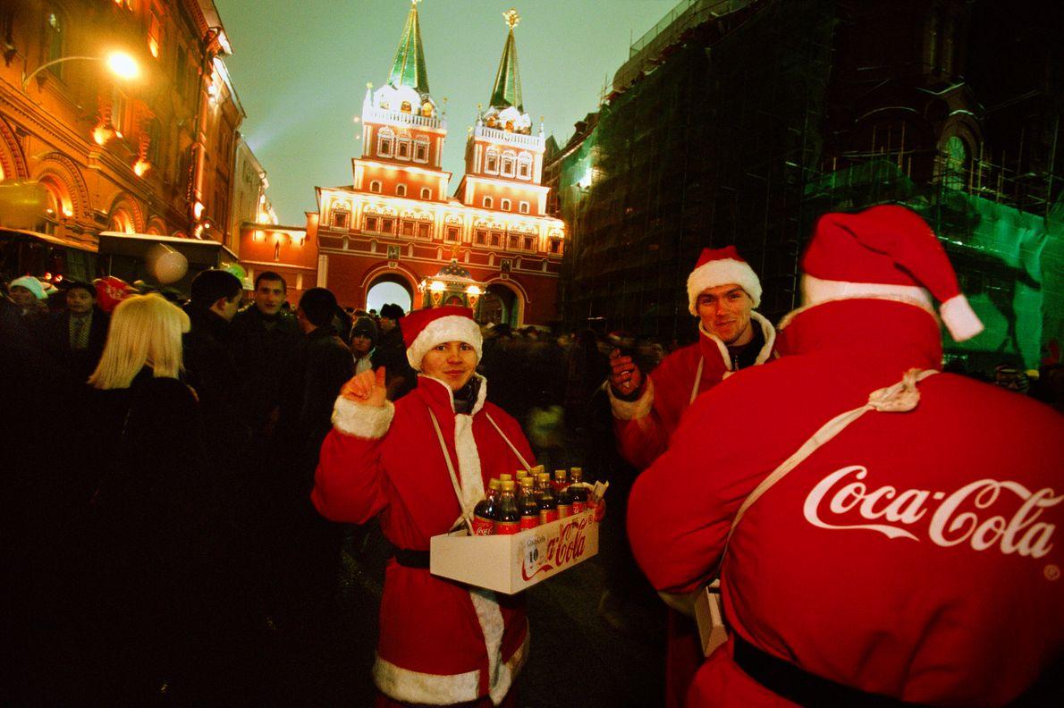 Verkleidet als Weihnachtsmänner verkaufen drei junge Männer Coca-Cola