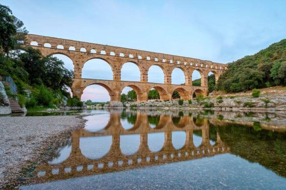 Über dem Fluss Gardon reihen sich die Bögen der Pont du Gard. Das römische Aquädukt aus ...