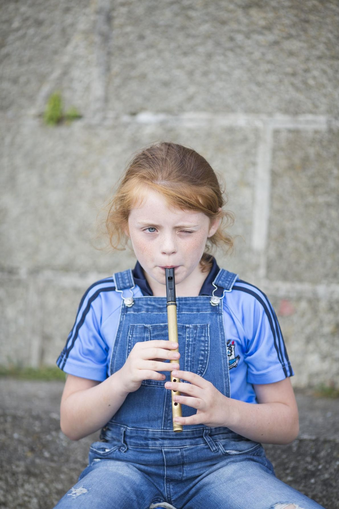 Ein junges Mädchen spielt ihre Irish flute an der Hafenmauer des Dorfes Howth, das etwa 30 ...