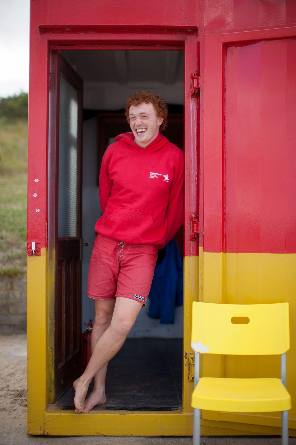 Ein Rettungsschwimmer steht in der Tür eines Häuschens am Portmarnock Beach, der auch als Velvet Strand ...