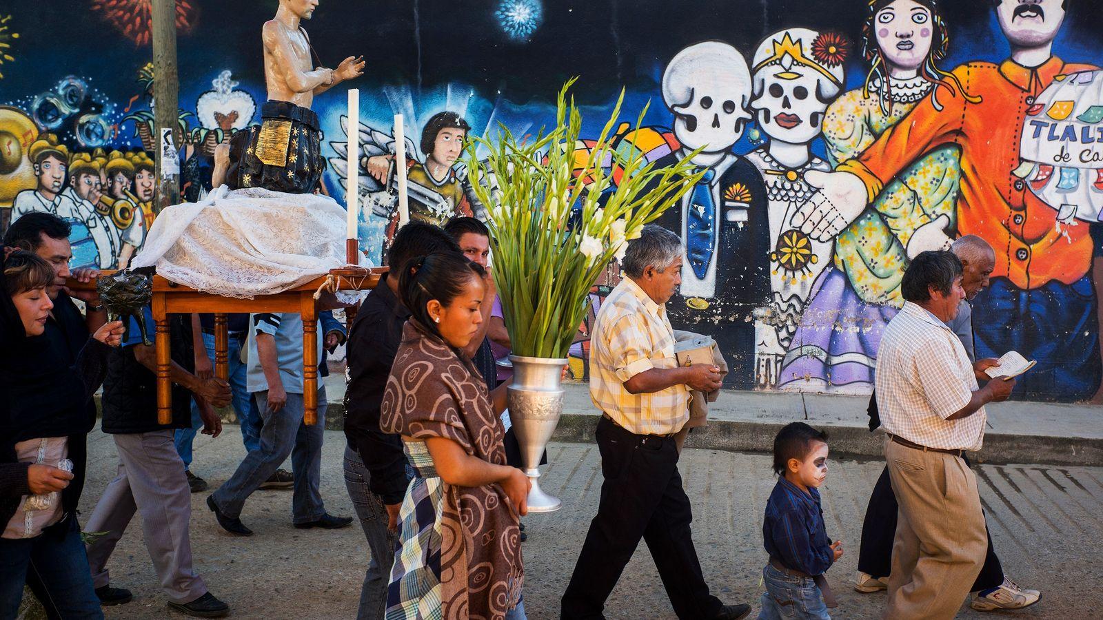 Während des Día de los Muertos laufen Menschen eine Straße voller Mauerbilder entlang.
