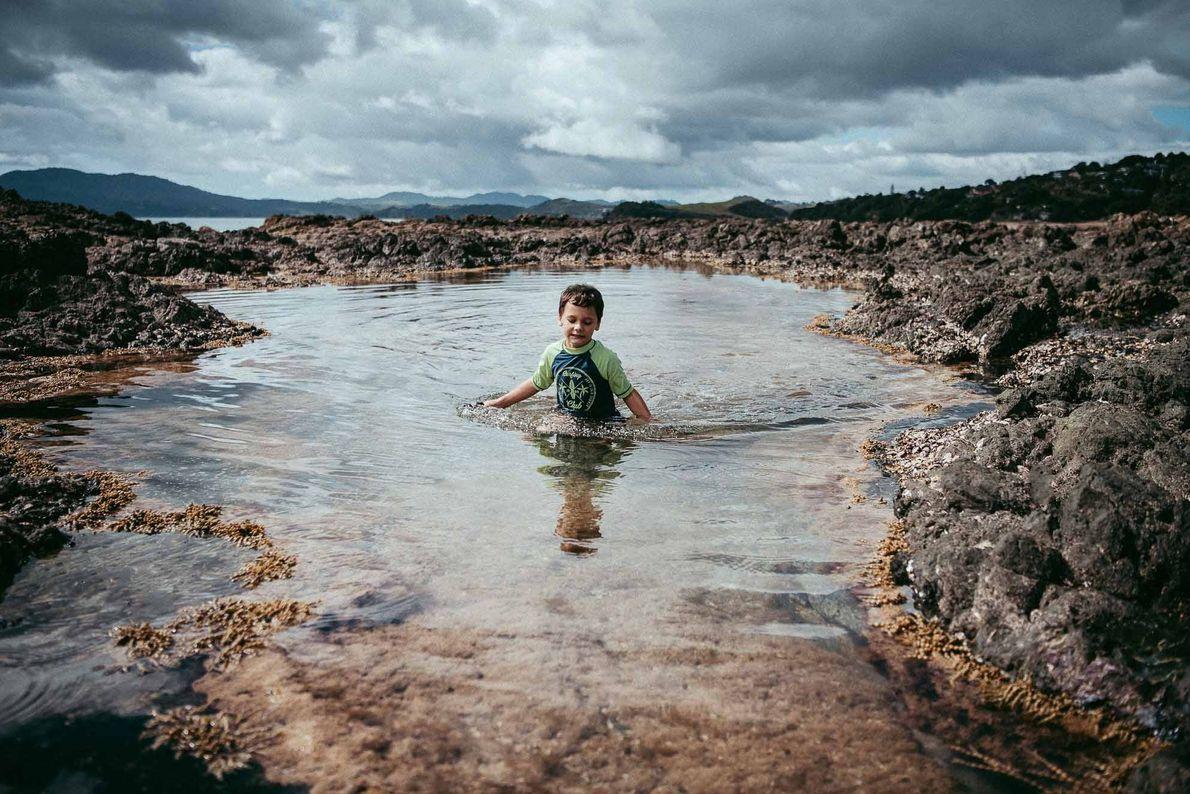 Ein Junge läuft an einem neuseeländischen Strand durch das Wasser.