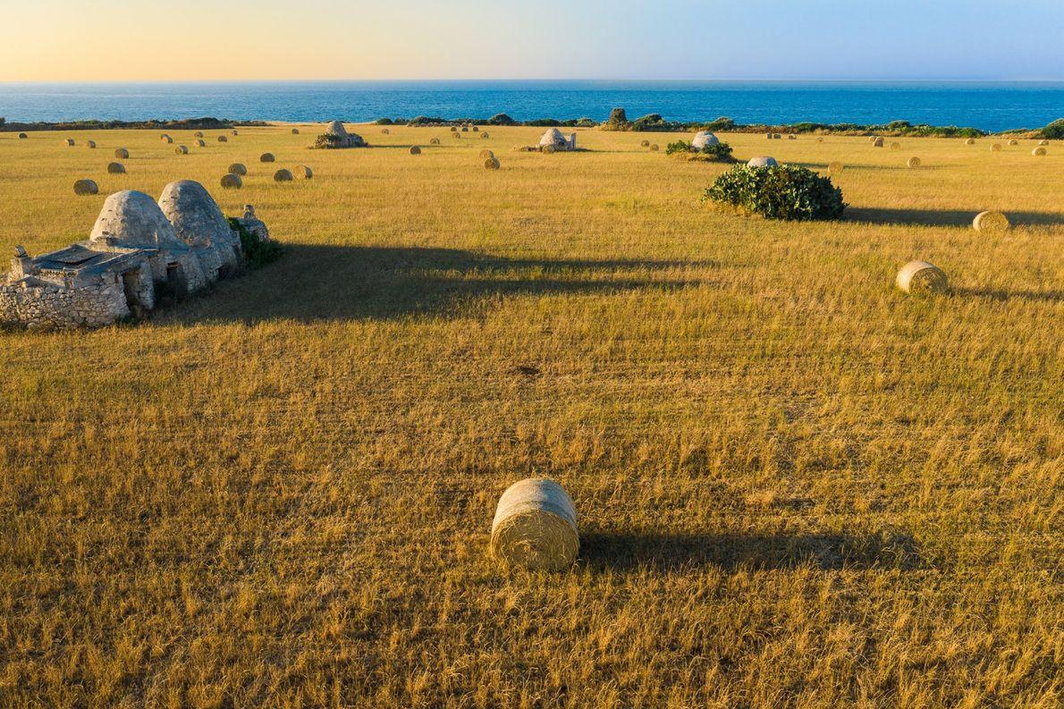 Heuballen liegen auf einem gemähten Weizenfeld in Polignano a Mare, einer Stadt an der Adriaküste in ...