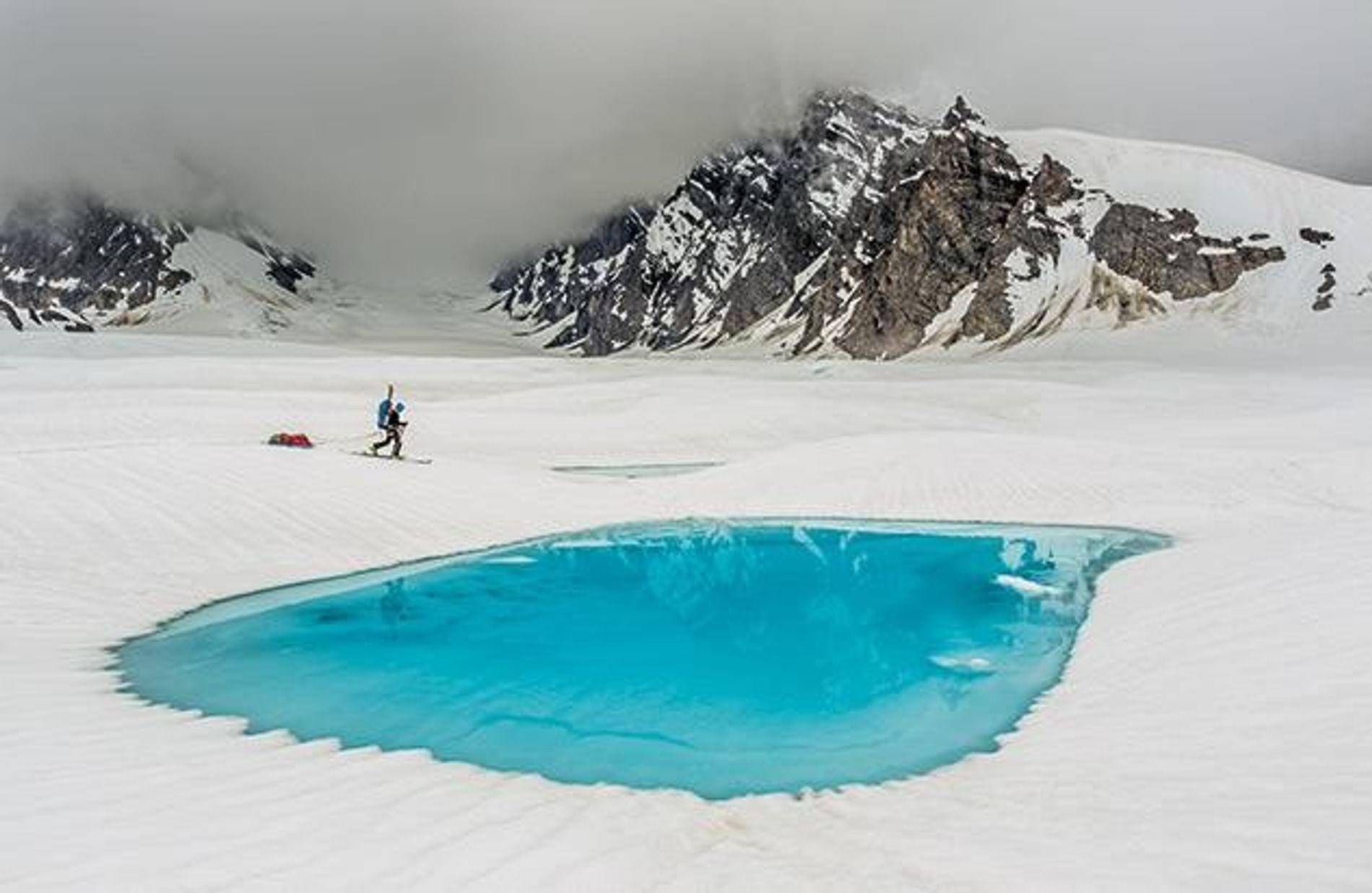 Unterwegs zu einer der vielen unbezwungenen Bergwände im Hochland des Denali passiert ein Bergsteiger auf Tourenskiern saphirblaues Schmelzwasser am Ruth-Gletscher.