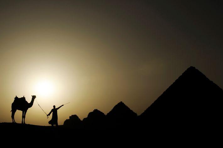 Die Sonne geht hinter der Nekropole von Gizeh im Außenbezirk von Kairo in Ägypten unter