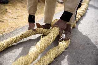 Ein Mann flicht neue Seile zu dicken Tauen, die später die Grundlage für die neue Brücke ...