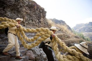 Die langen, schweren Taue werden zur Schlucht hinabgetragen, um mit dem Brückenbau zu beginnen.
