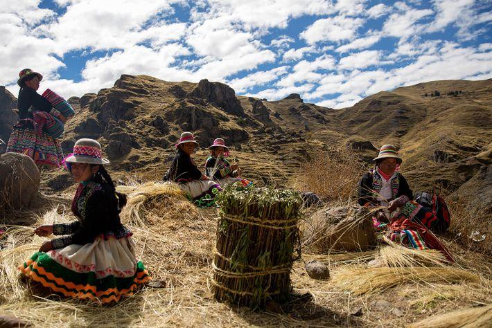 Quechua-Frauen sitzen auf der Ebene neben der Schlucht und flechten das Ichu-Gras zu Seilen. Während der ...