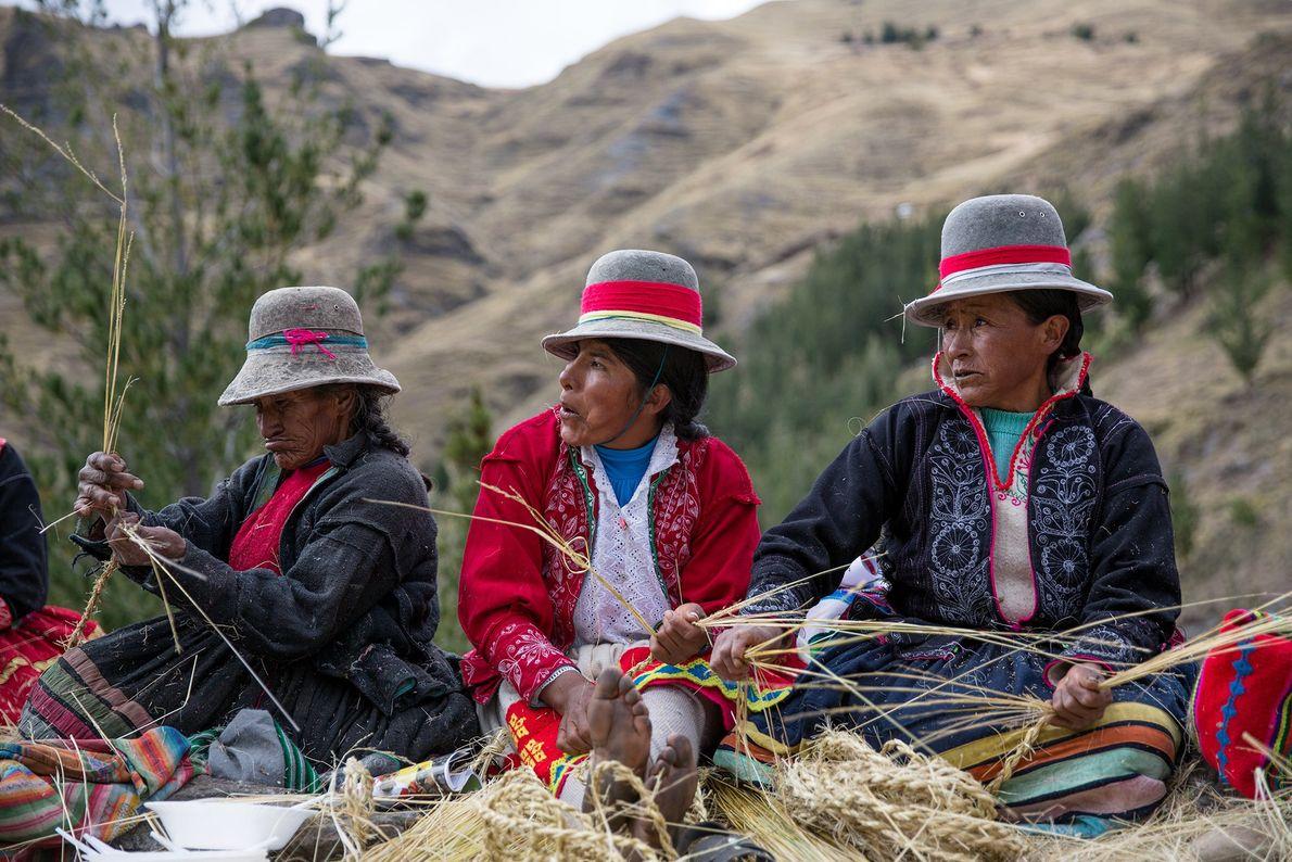 Bunt gekleidete Quechua-Frauen flechten auf der Ebene neben der Schlucht Seile aus Ichu-Gras.