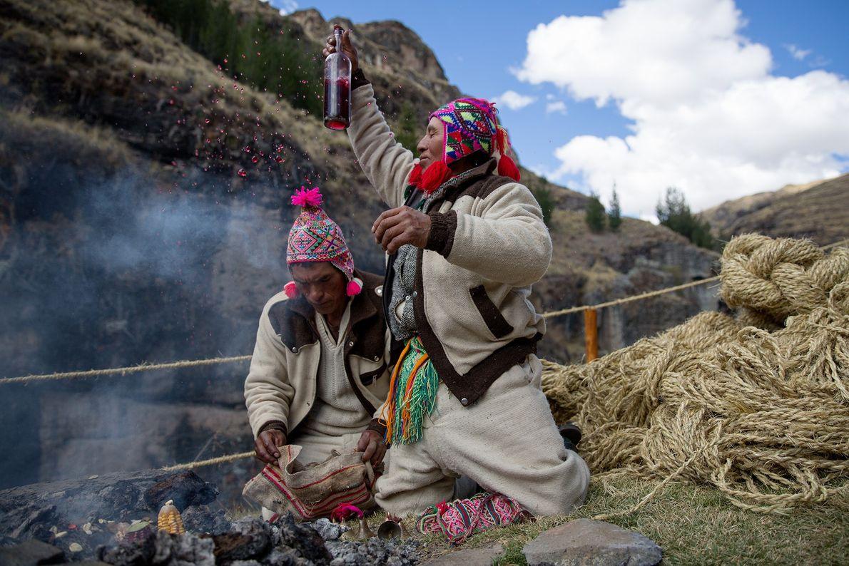Am Rande der Brücke bringen Priester der Quechua Opfergaben dar.
