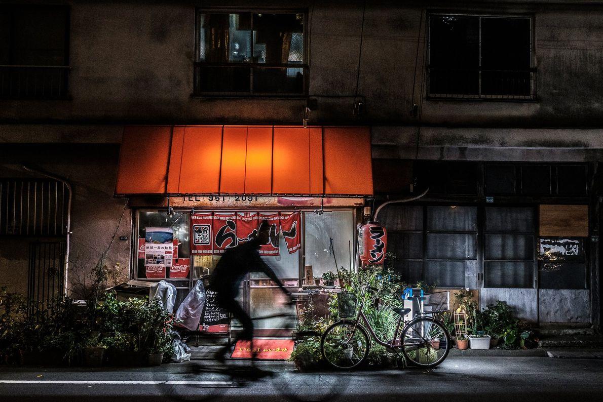 Ein Radfahrer fährt gegen Mitternacht an einem kleinen Ramen-Shop in Nakano vorbei, einem geschäftigen Bezirk westlich ...