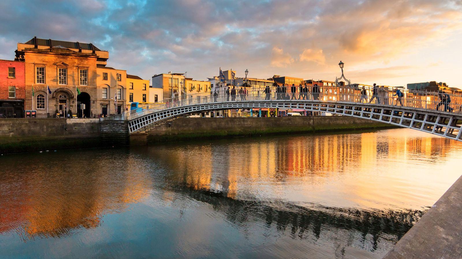 Goldene Lichtstrahlen lassen das Wasser unter der Ha'penny Bridge im irischen Dublin schimmern.