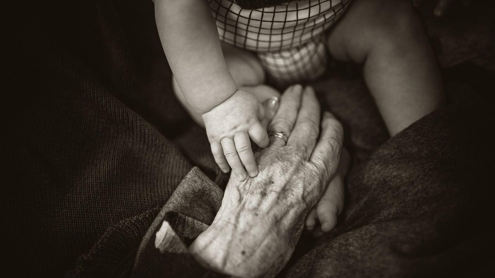 Hand einer Seniorin berührt Bein eines Kleinkinds