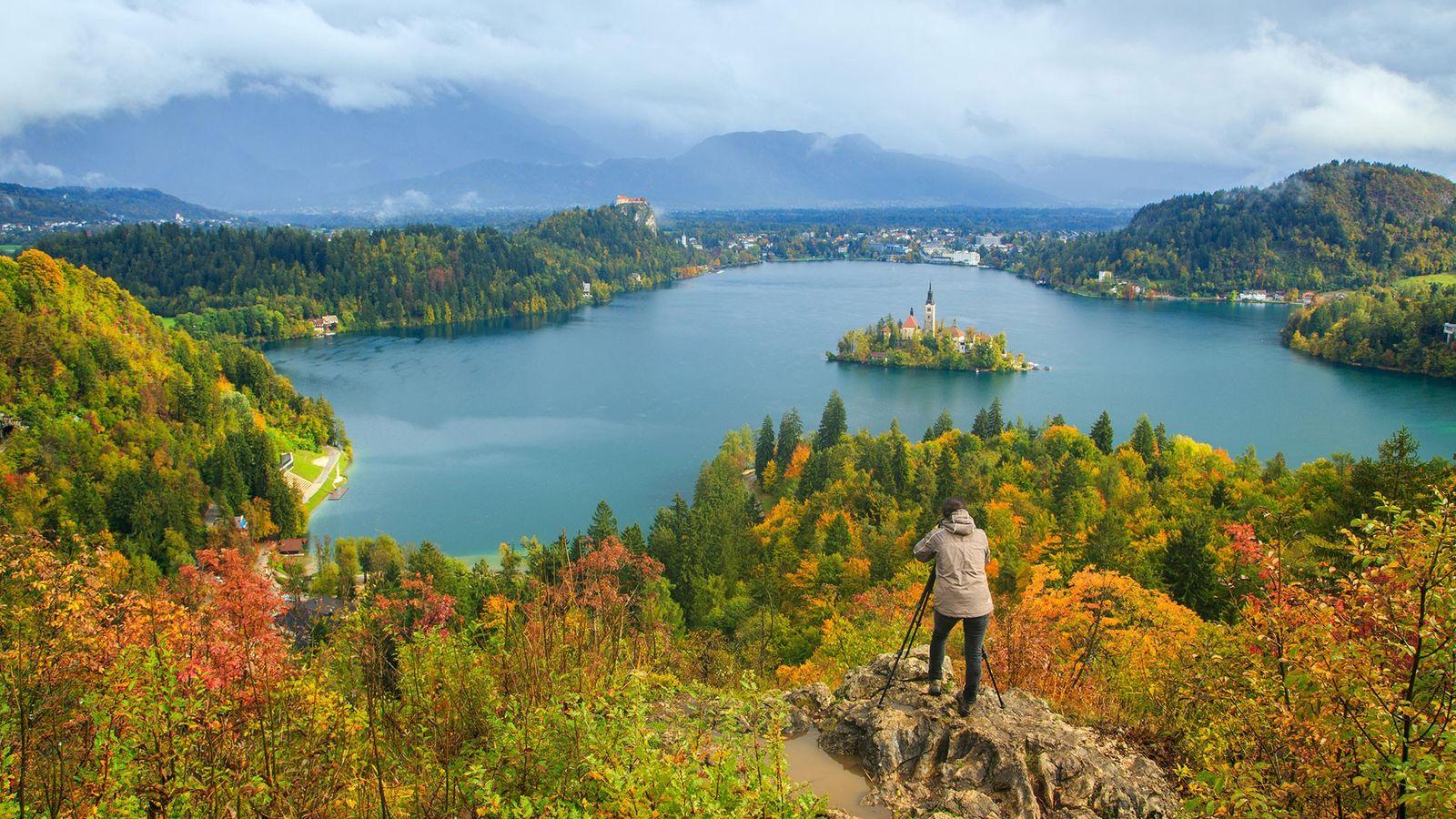 Ein Fotograf richtet sein Objektiv auf den Bleder See in den Julischen Alpen in Slowenien aus.