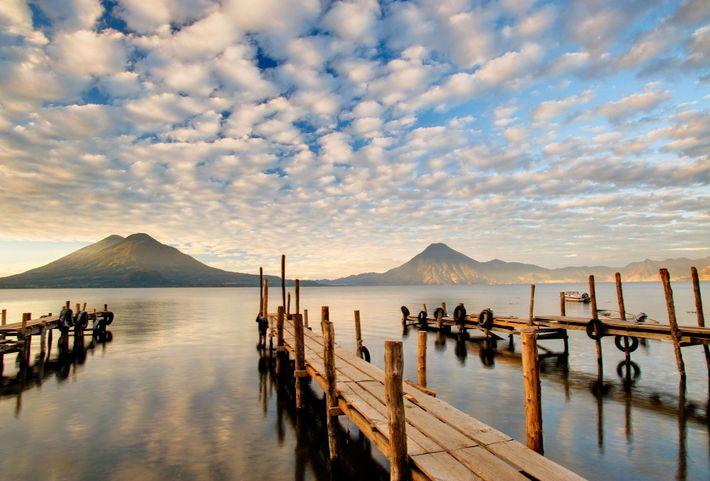 Holzstege ragen in den Lago de Atitlán in Guatemala.