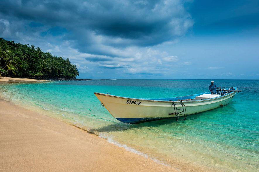 Ein Boot landet am Sandstrand Banana Beach in São Tomé und Príncipe an.