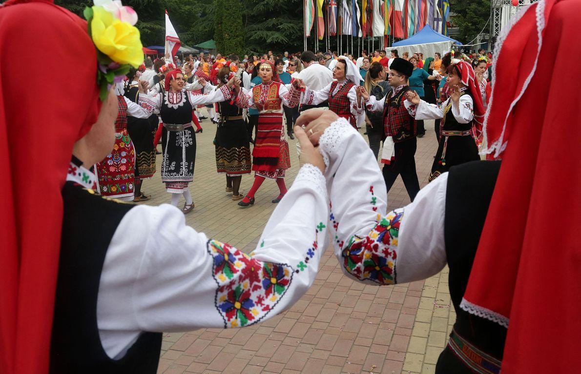 Männer und Frauen fassen sich an den Händen und führen einen traditionellen Volkstanz auf, der sich ...