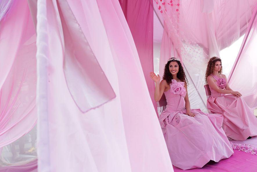 Die Rosenkönigin Mihaela Hadzhieva sitzt während einer Parade auf ihrem rosafarbenen Thron und winkt.