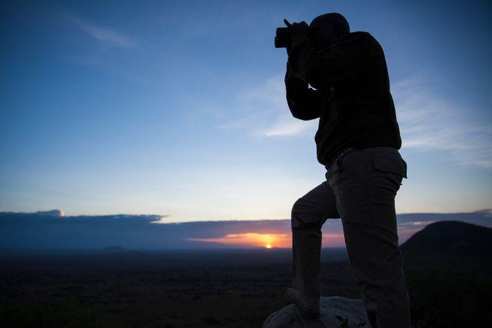 Ein Safariführer von der ol Donyo Lodge blickt in den Chyulu Hills in Kenia bei Sonnenuntergang ...