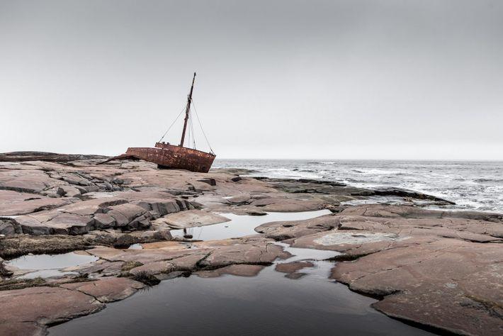Die rostige Hülle eines Frachtschiffs liegt an der felsigen Küste bei Kegaska.