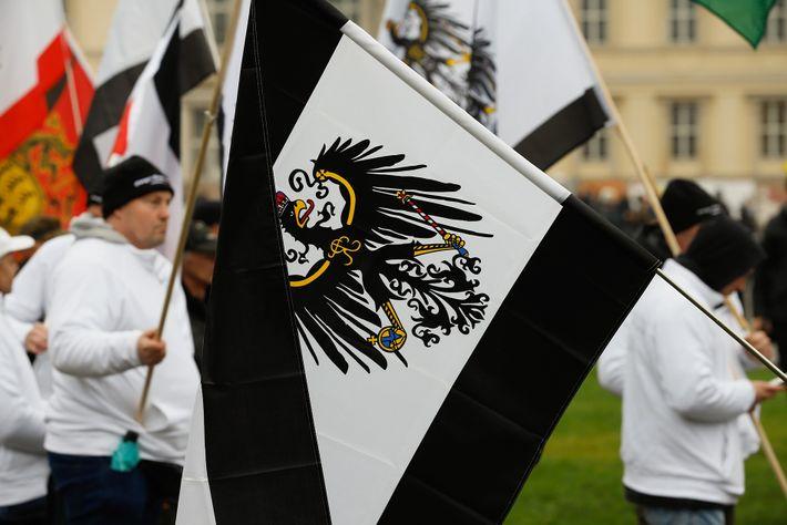 Eine Menschentraube schwenkt Reichsbürgerflaggen vor dem Reichstag. Zu den von sogenannten Reichsbürgern vertretenen Ideologien gehören oft ...