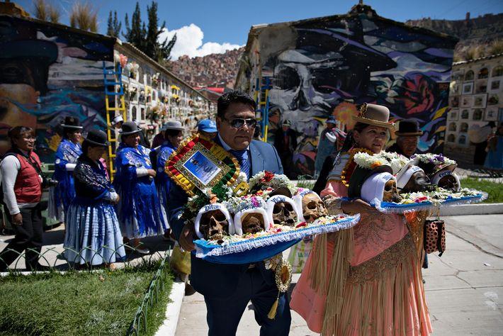 Hinter den Anhängern, die Ñatitas tragen, erstrecken sich die Gänge des Generalfriedhofs endlos wie eine kleine ...