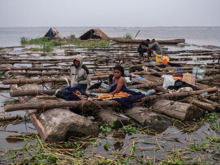 Merveille Mbombahundu und Dieu Yanick auf ihrem selbstgebauten Floß, auf dem sie seit mehreren Monaten leben.