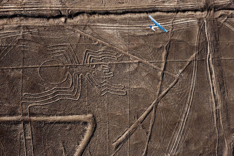 Ein Flugzeug gleitet über die antike Geoglyphe einer Spinne in der peruanischen Wüste.