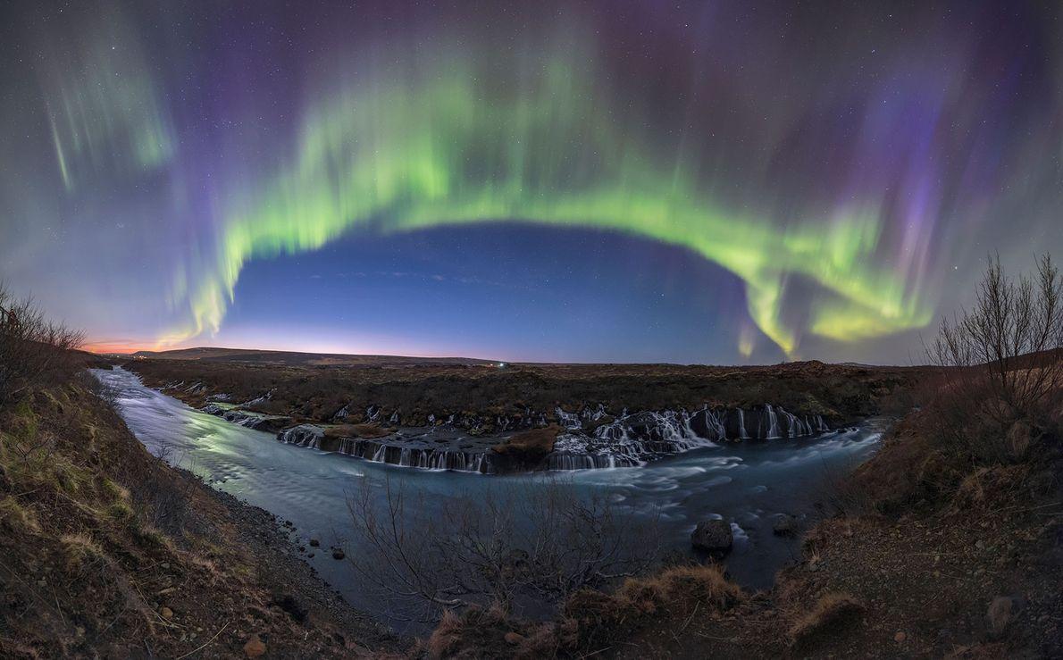 Grün und violett schimmernde Polarlichter ziehen sich über den Wasserfällen entlang des Flusses Hvita auf Island ...