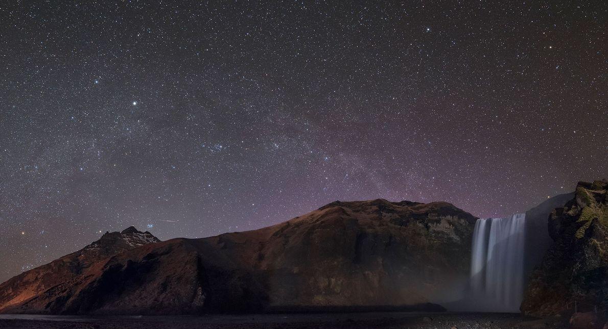 Sternkonstellationen wie Orion und Perseus schimmern über dem Skógafoss-Wasserfall auf Island.