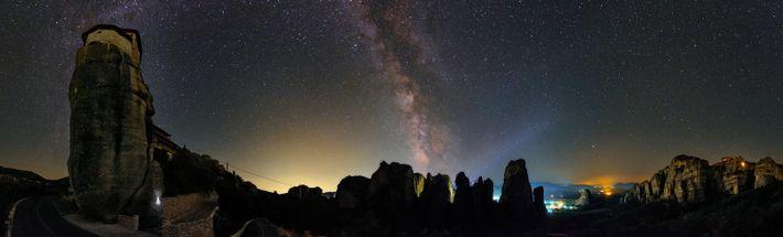 Die Milchstraße und das Licht der Stadt Kalambaka erstrahlen hinter den Metéora-Klöstern in Griechenland.