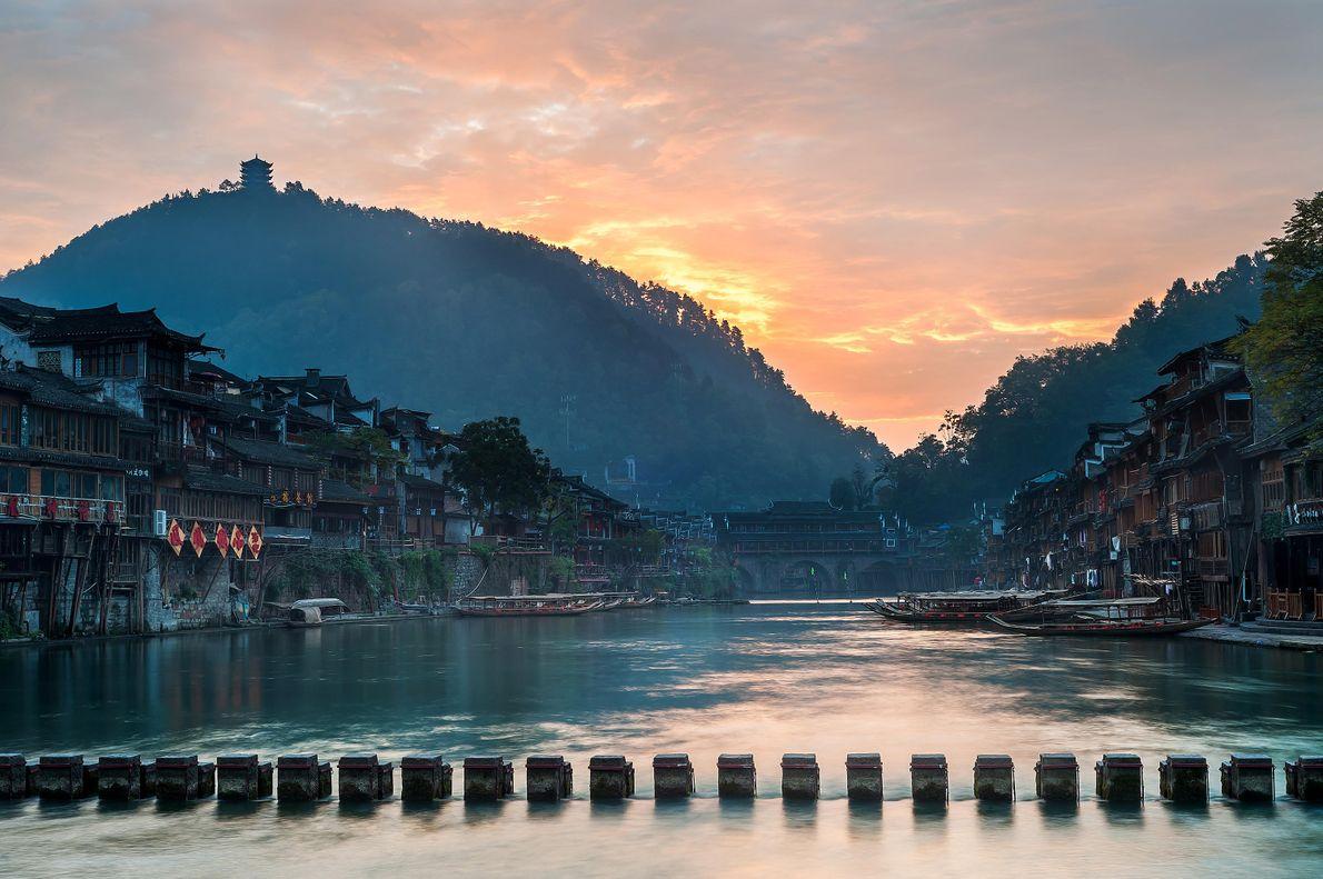 Eine traditionelle Dingbu-Brücke aus geschnittenen und im Fluss versenkten Steinen führt über den Tuojiang in der ...