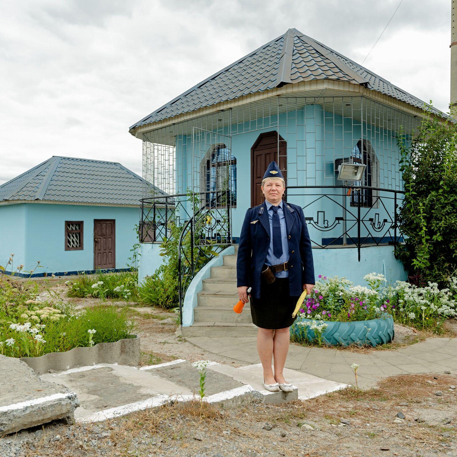 Schienenwärterin vor einem Bahnwärterhaus in der Ukraine