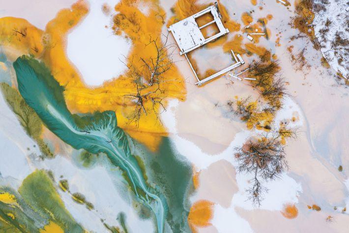 Eine alte Tür, in grünem und gelbem Schlamm schwimmend. Der Schlamm stammt aus einer giftigen Kupfermine