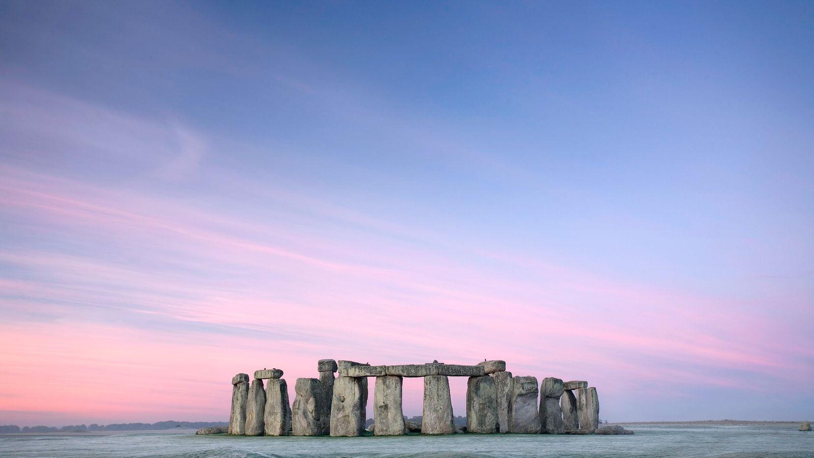 Rosa- und lilafarbene Streifen zeigen sich in der Morgendämmerung am Himmel über Stonehenge.