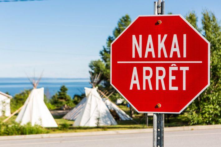 Stoppschilder in Les Escoumins sind auf Französisch und Innu-Aimum (eine algonquische Sprache) beschriftet. Die Gemeinde ist ...