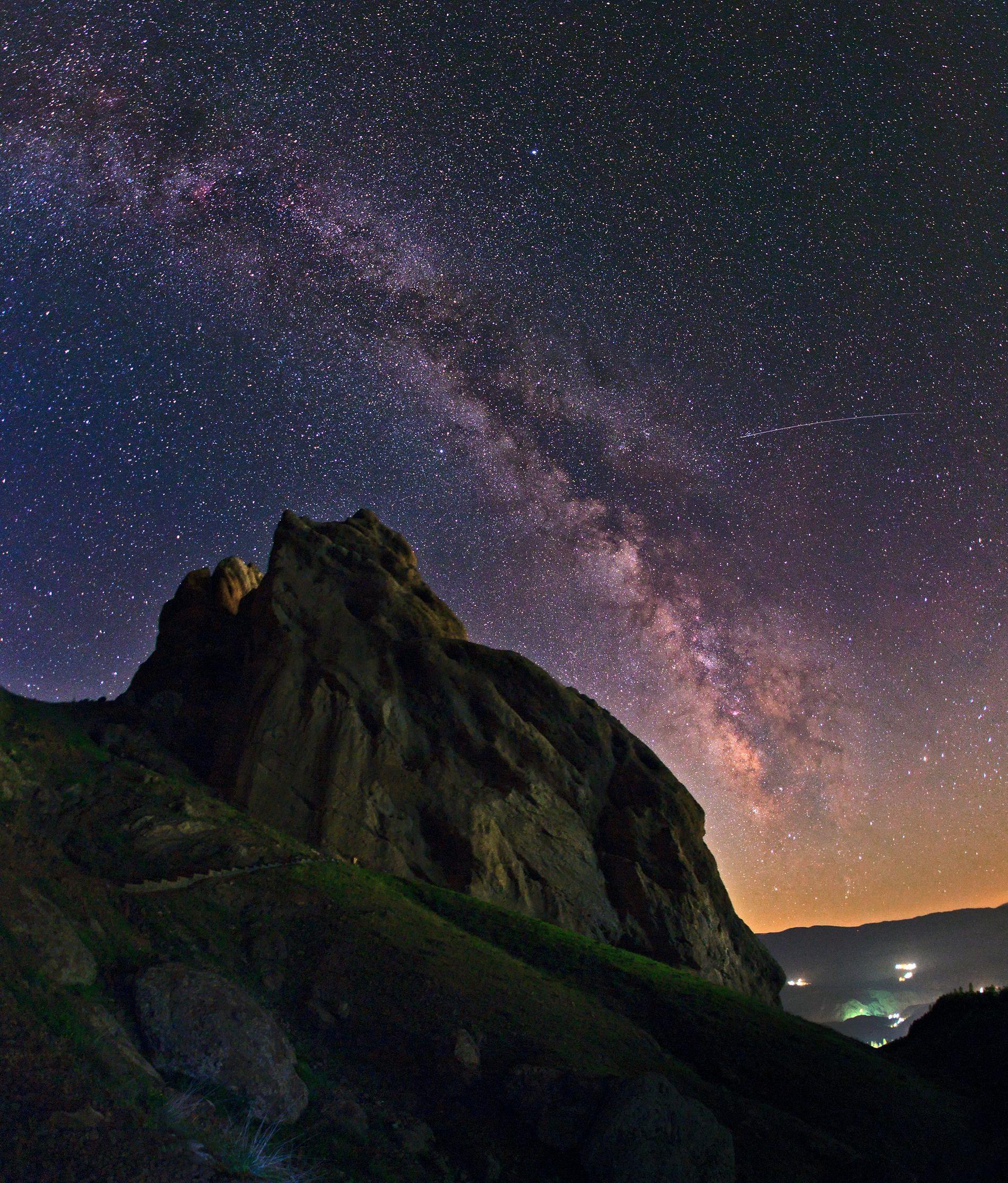 Ein Meteor zieht am Himmel eine leuchtende Spur hinter sich her und scheint geradewegs in die ...